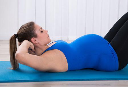 خانمی پس از دورهی بارداری در حال تمرین برای رسیدن به تناسب اندام